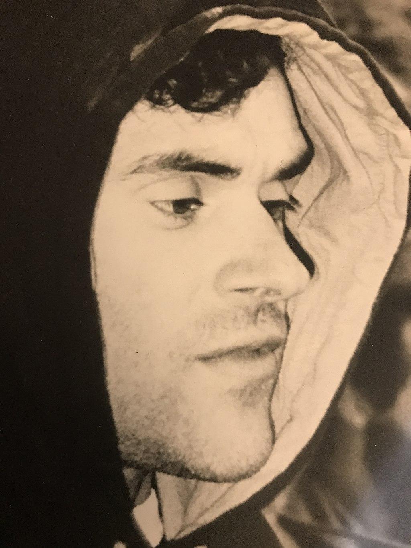 A moody face shot of Jerry Moffatt wearing a hoodie